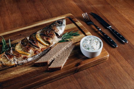grilled fish with lemon and sauce on wooden board