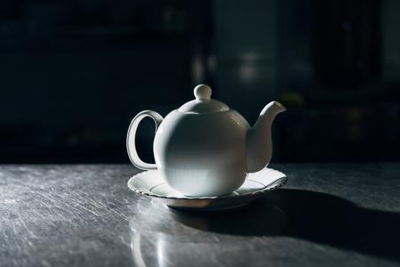 teapot on plate on metal surface in dark room