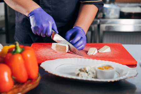 chef slicing cheese for cheese plate