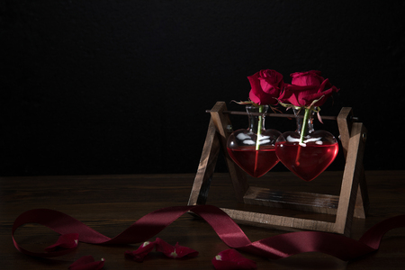 two red roses in heart shaped vases on wooden stand