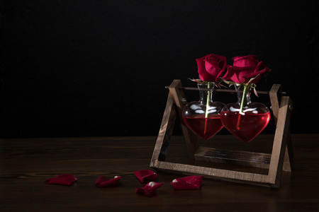 two red roses in heart shaped vases on wooden stand and petals on table Stok Fotoğraf