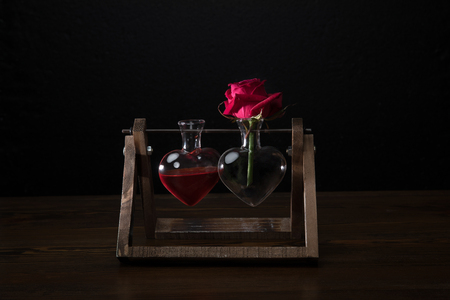 Red Rose In Heart Shaped Vase And Vase With Love Elixir Stock Photo