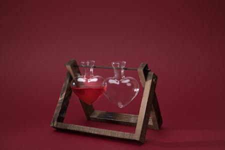 heart shaped glass jar with perfume and empty glass jar on wooden stand on red Stock Photo