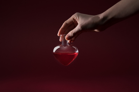 cropped image of woman holding heart shaped glass jar of love potion isolated on red Stock Photo