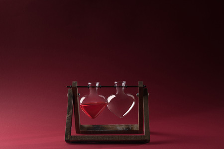 heart shaped glass jar with perfume and empty glass jar on wooden stand on red Stock Photo - 93894957