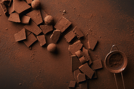 top view of arrangement of various types of chocolate, truffles and sieve with cocoa powder 스톡 콘텐츠