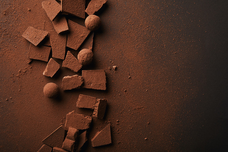 flat lay with arranged truffles and chocolate bars with cocoa powder on tabletop