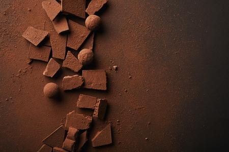 flat lay z ułożonymi truflami i tabliczkami czekolady z proszkiem kakaowym na blacie