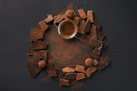 top view of arrangement of various types of chocolate, truffles and sieve on grey tabletop