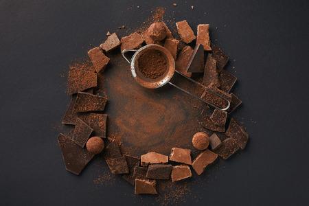 Vista dall'alto della disposizione di vari tipi di cioccolato, tartufi e setaccio su tavolo grigio Archivio Fotografico - 93895016