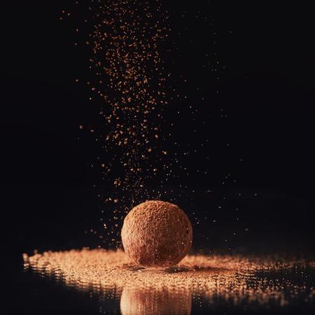 close-up van zoete truffelsuikergoed met cacaopoeder op zwart