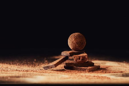 close up view of truffle on chocolate bars with cocoa powder on black