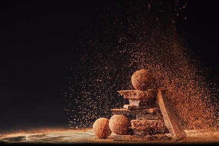 トリュフとチョコレートバーのアレンジのクローズアップビューと黒のココアパウダー 写真素材
