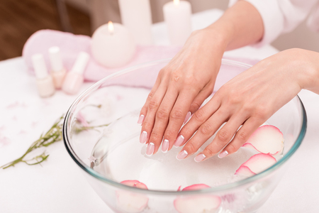 close-up view of female hands receiving spa treatment in glass bowl with rose petals Imagens