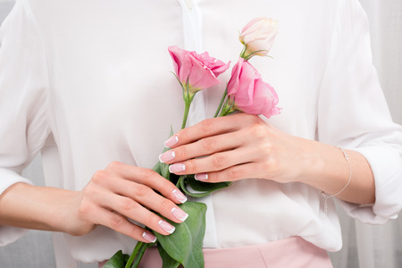 young woman holding beautiful eustoma flowers in hands