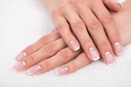close-up view of beautiful female hands with french manicure on white