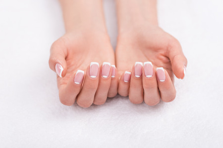 close-up view of beautiful female hands with french manicure on white Stock Photo - 93893348