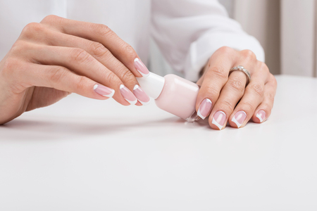 cropped shot of woman holding nail polish while doing manicure Banco de Imagens