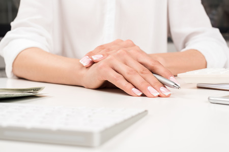 female hands with beautiful manicure holding pen at workplace