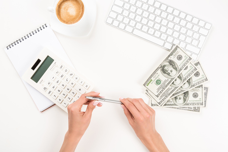 職場で電卓とドル紙幣で働くビジネスウーマン