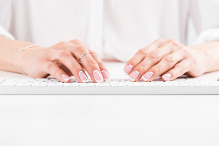 top view of female hands with beautiful manicure typing on keyboard