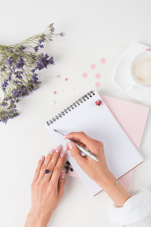 Young woman with french manicure writing in notebook