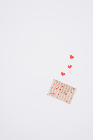 top view of decorated valentines day envelope with tiny hearts isolated on white