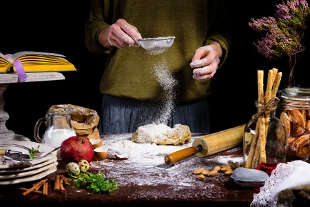 person sifting flour on dough at table with ingredients