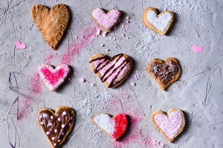 various sweet heart shaped valentines cookies on grey surface