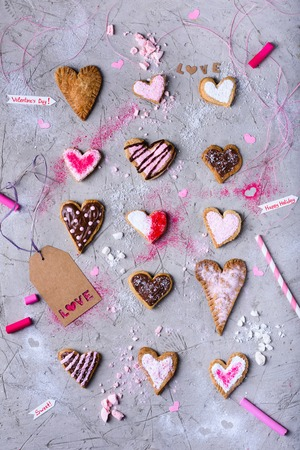 sweet tasty heart shaped cookies with love label on grey cracked surface