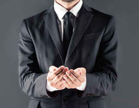 cropped view of businessman in suit with open hands