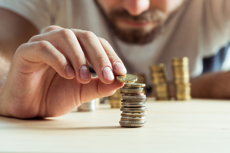 cropped view of man stacking coins on table