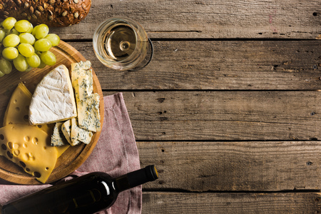 top view of bottle of white wine, wineglass, different cheese and bread on wooden tabletop with copy space