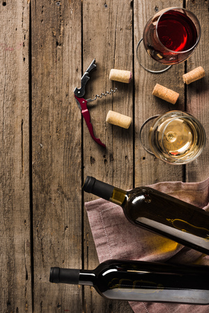 top view of two bottles of wine, corkscrew and wineglasses on wooden tabletop with copy space