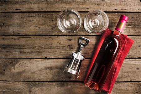 top view of bottle of pink wine on napkin, corkscrew and two empty wineglasses on wooden tabletop with copy space