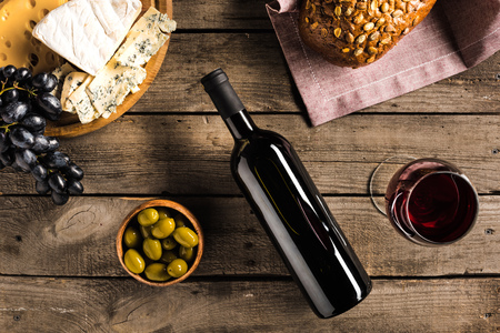 top view of bottle of red wine, wineglass, green olives, different cheese and bread on napkin on wooden tabletop