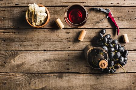 ピンクワイン、コルクスクリュー、ワイングラス、ボウルのチーズ、木製の卓上のブドウのボトルのトップビュー 写真素材
