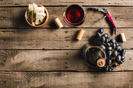 top view of bottle of pink wine, corkscrew, wineglass, cheese in bowl and grapes on wooden tabletop with copy space