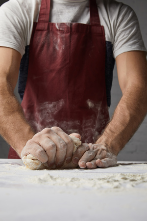 cropped image of chef kneading dough on table in kitchen