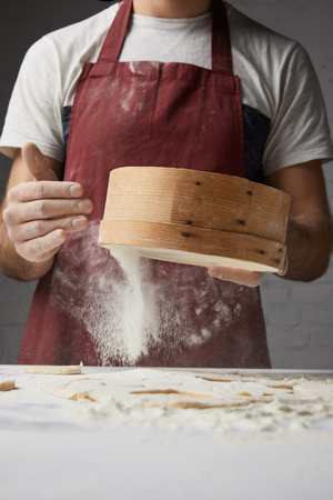 cropped image of chef sifting flour with sieve  Stock Photo