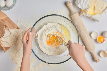 반죽을 준비하고 밀가루와 계란을 휘젓는 요리사의 자른 이미지