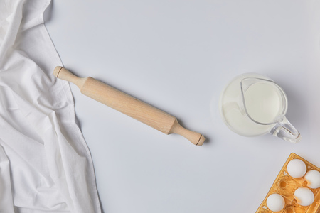 top view of tablecloth, rolling pin and milk on table