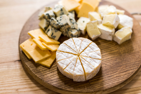 variety of cheese kinds on wooden board 版權商用圖片