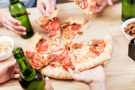 friends eating pizza together Banco de Imagens