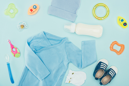 baby clothes and accessories with milk isolated on blue Stock Photo