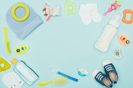 baby clothes, equipment and milk isolated on blue Foto de archivo