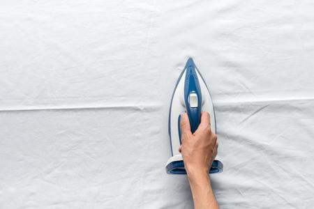 man ironing bed sheets Archivio Fotografico