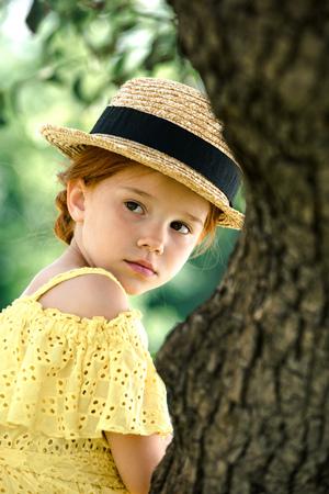 pensive girl in straw hat