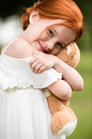 redhead girl with teddy bear Stock Photo