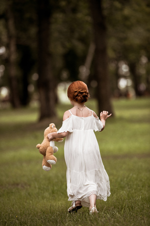 back view of cute little girl in white dress holding teddy bear while walking in park